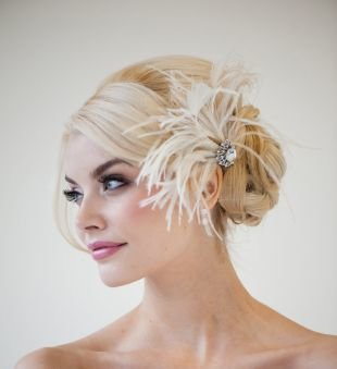 Цвет волос теплый блонд, свадебная прическа с низким пучком из кос и перьями