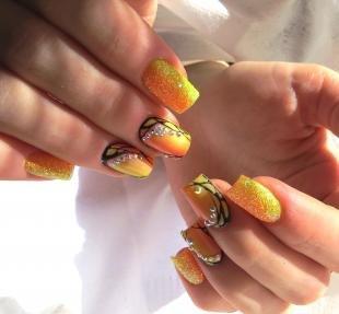 Осенние рисунки на ногтях, оранжевый маникюр с черным узором и стразами